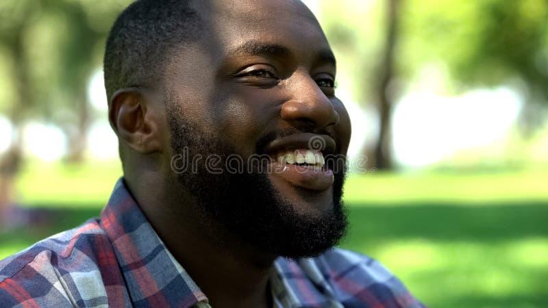 Uśmiechniętego amerykanin afrykańskiego pochodzenia brodaty mężczyzna relaksuje outdoors, cieszący się życie, szczęście fotografia stock
