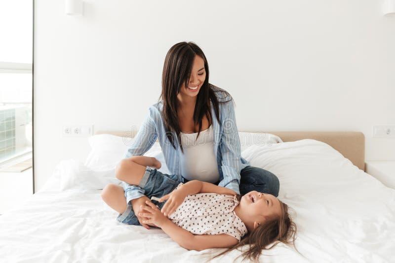 Uśmiechniętego azjata macierzysty bawić się z jej małą córką na łóżku zdjęcia royalty free