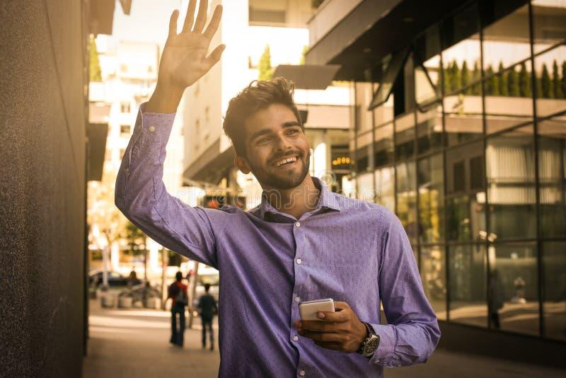 Uśmiechniętego biznesmena synkliny chodząca ulica i mówi someo cześć zdjęcie royalty free