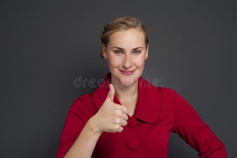 Uśmiechniętego biznesowej kobiety kciuka up przedstawienie odosobniony ciemny tło obraz royalty free
