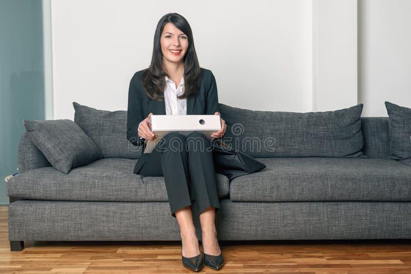 Uśmiechniętego bizneswomanu siedzący mienie segregator zdjęcie stock