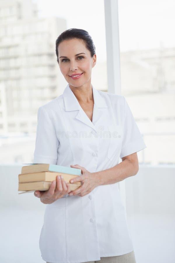 Uśmiechniętego doktorskiego mienia medyczne książki zdjęcie stock