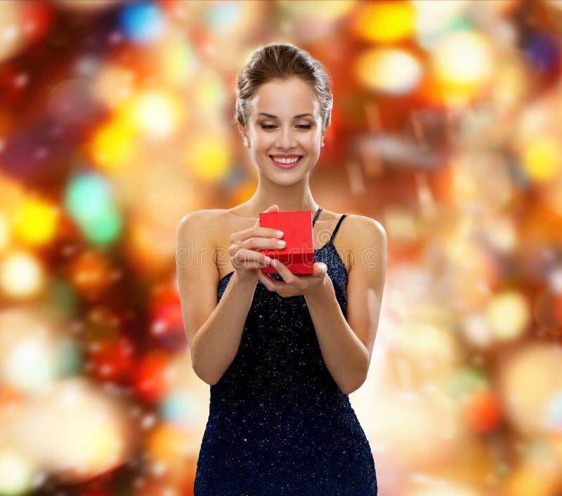 Uśmiechniętego kobiety mienia prezenta czerwony pudełko obraz stock