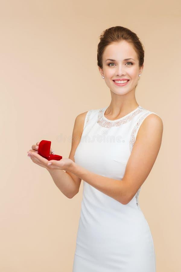 Uśmiechniętego kobiety mienia prezenta czerwony pudełko z pierścionkiem fotografia stock