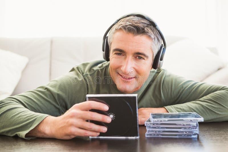 Uśmiechniętego mężczyzna mienia i muzyki słuchający cd obrazy stock