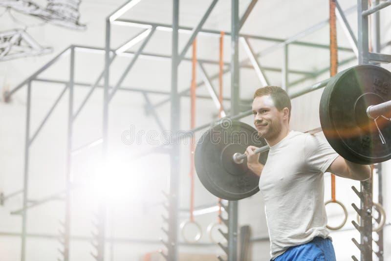 Uśmiechniętego mężczyzna podnośny barbell przy crossfit gym obrazy royalty free