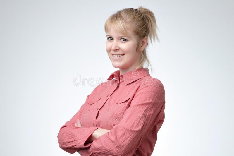 Uśmiechniętego młodego blondynu studencka patrzeje kamera fotografia stock