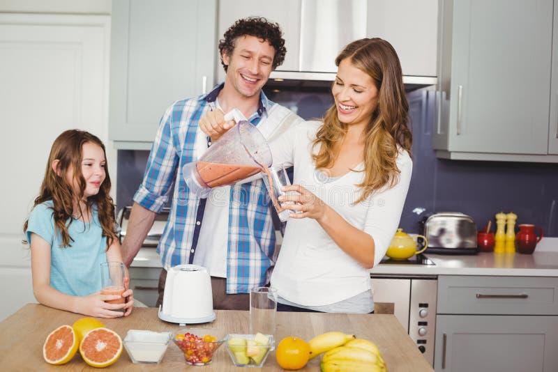 Uśmiechniętego macierzystego dolewania owocowy sok w szkle z rodziną fotografia stock