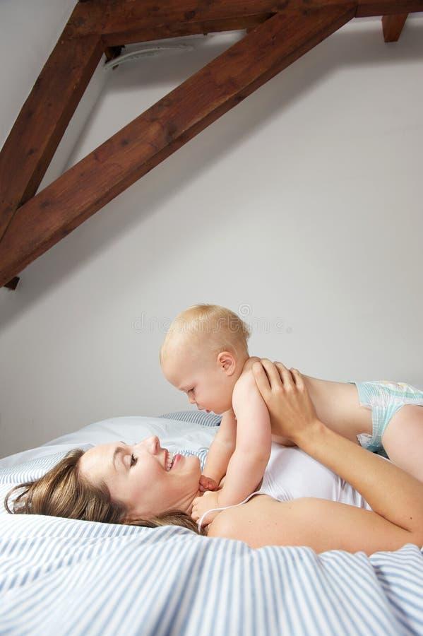 Uśmiechniętego macierzystego mienia śliczny dziecko w łóżku zdjęcie royalty free