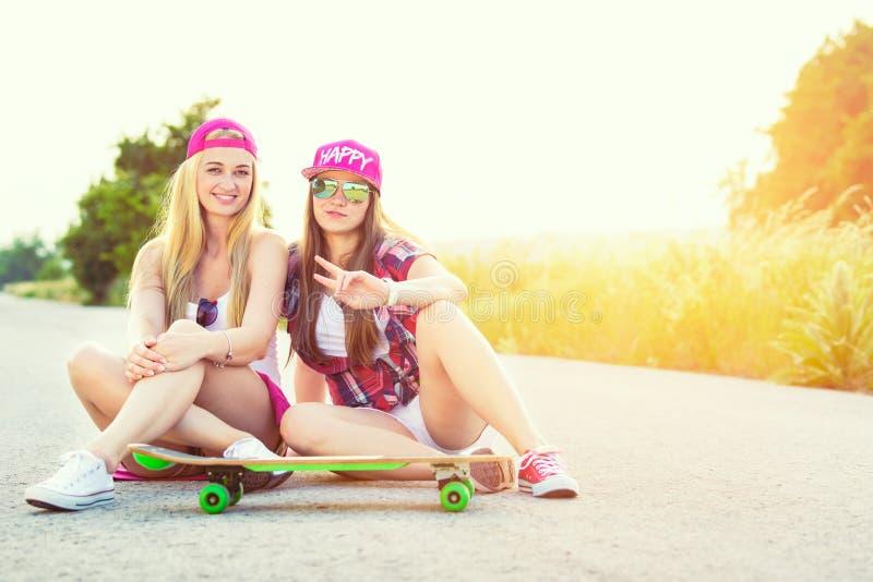 Uśmiechniętego modnisia nastoletni przyjaciele z deskorolka, colorised wizerunek z sunflare obraz royalty free