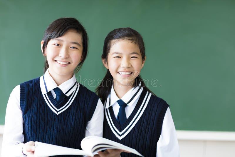 Uśmiechniętego nastolatka studenckie dziewczyny w sala lekcyjnej obrazy royalty free