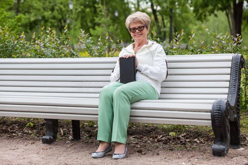 Uśmiechniętego starszego kobiety obsiadania długa biała ławka z czarną książką w ręce, patrzeje kamerę zdjęcia royalty free