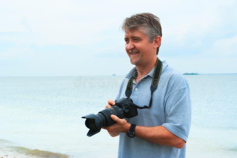 Uśmiechniętego szczęśliwego mężczyzna plenerowy fotograf z kamerą fotografia stock