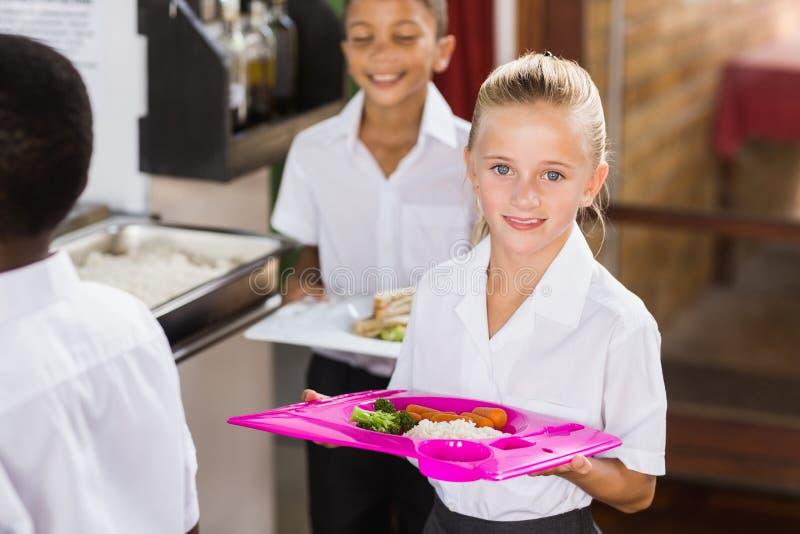 Uśmiechniętego uczennicy mienia karmowa taca w szkolnym bufecie zdjęcie stock