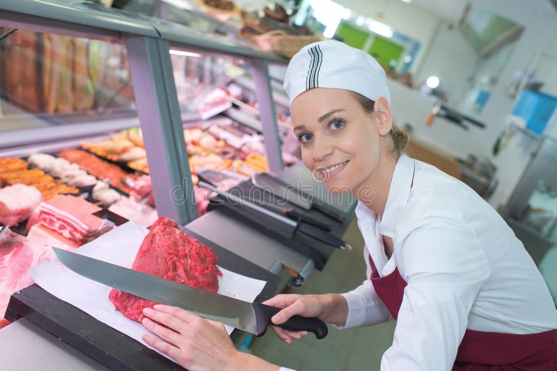 Uśmiechniętej żeńskiej masarki tnący mięso zdjęcie stock