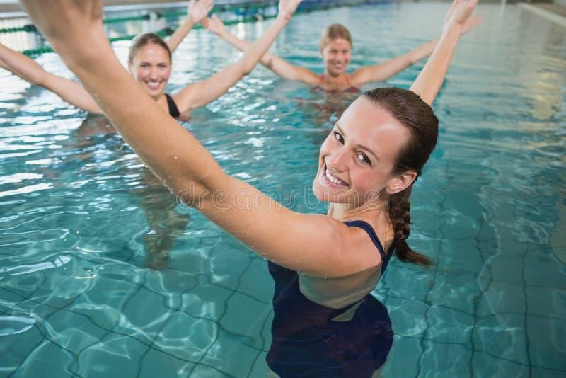 Uśmiechniętej żeńskiej sprawności fizycznej aqua klasowi robi aerobiki zdjęcia royalty free