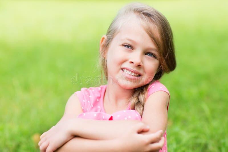 Uśmiechniętej blond dziewczyny przyglądający up zdjęcia stock