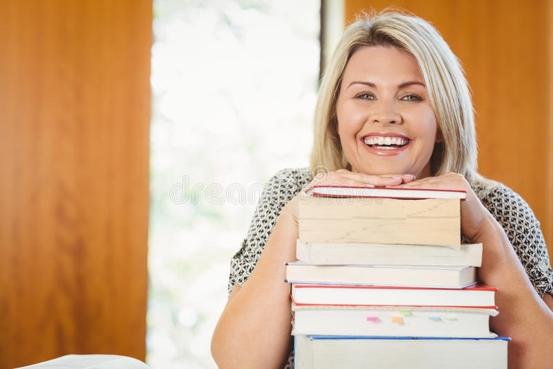Uśmiechniętej blondynki dojrzały uczeń z stertą książki obraz stock