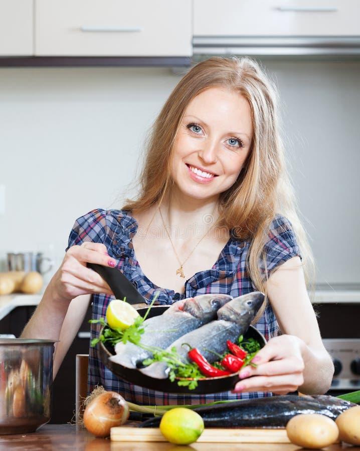 Uśmiechniętej blondynki kobiety kulinarny lubina w smażyć nieckę zdjęcie stock