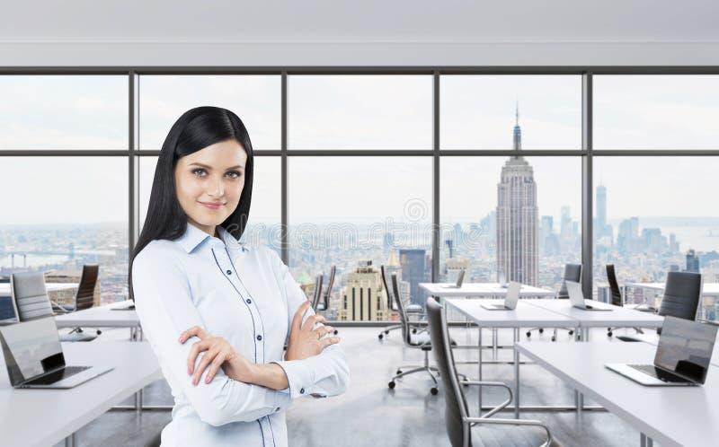 Uśmiechniętej brunetki biznesowa dama z przecinającymi rękami stoi w nowożytnym panoramicznym biurze w Miasto Nowy Jork Manhattan obrazy royalty free
