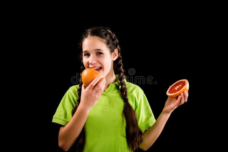Uśmiechniętej dziewczyny degustaci pokrojony czerwony grapefruitowy fotografia royalty free