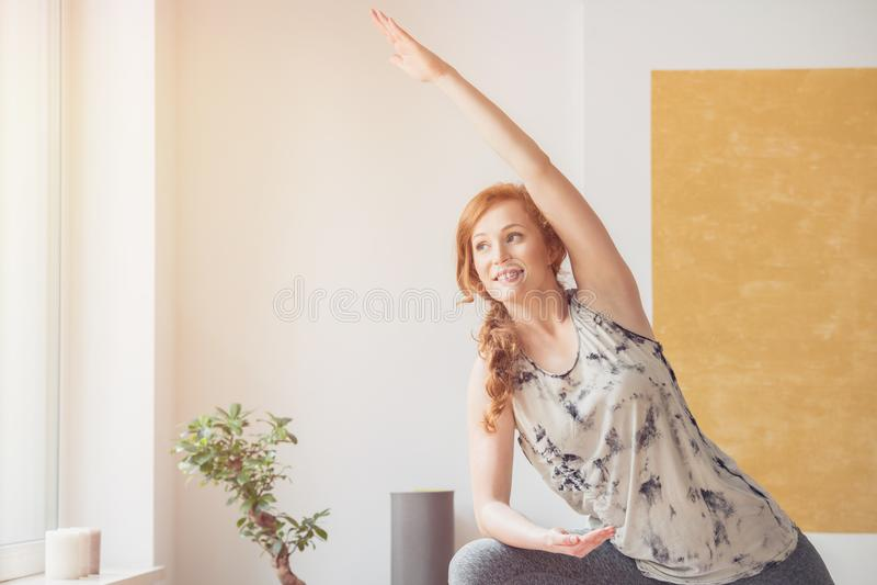 Uśmiechniętej imbirowej kobiety ćwiczy joga zdjęcie stock