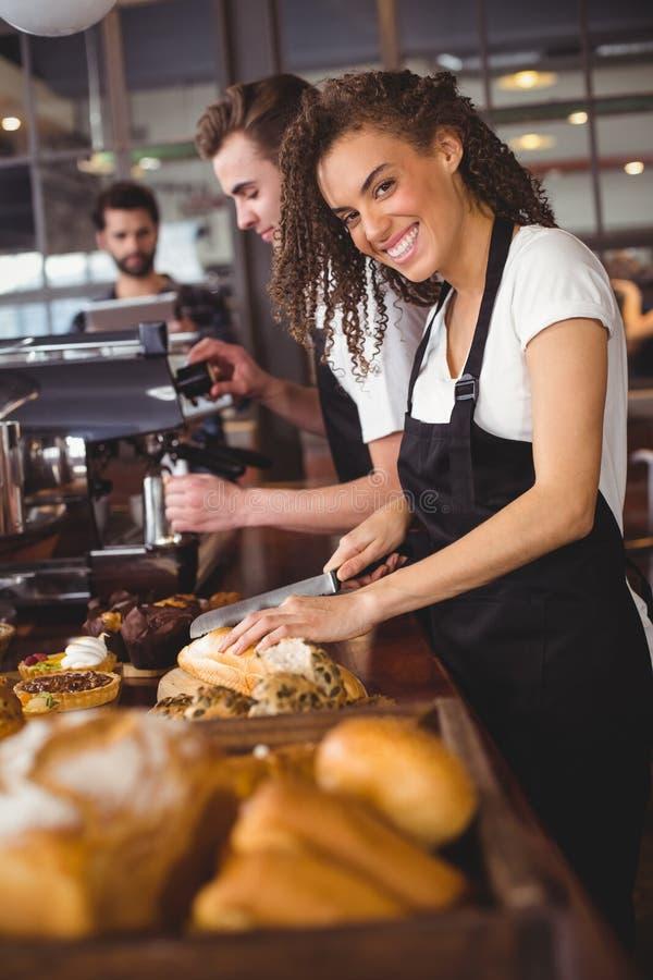 Uśmiechniętej kelnerki tnący chleb przed kolegą obraz stock