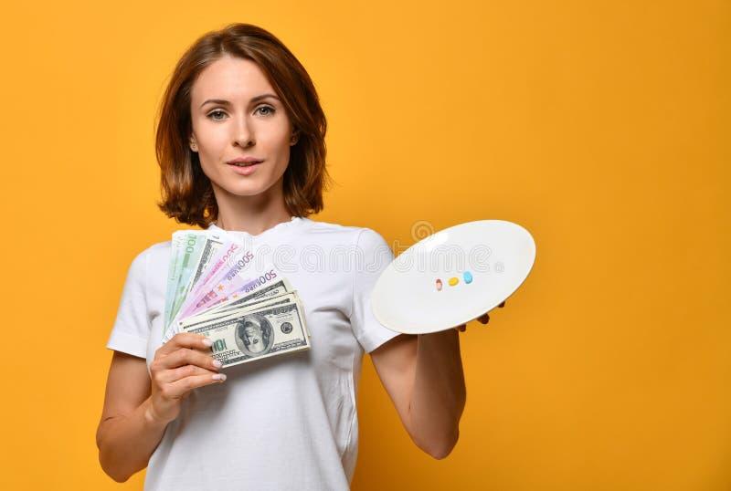 Uśmiechniętej kobiety chwyta żywiony talerz z różnymi kolor pigułek diety nadprogramów lekami na receptę i dolarami pieniądze na  obrazy royalty free