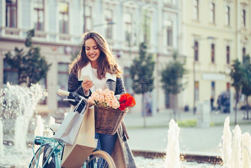 Uśmiechniętej kobiety pisać na maszynie wiadomość tekstowa na mądrze telefonie obrazy royalty free