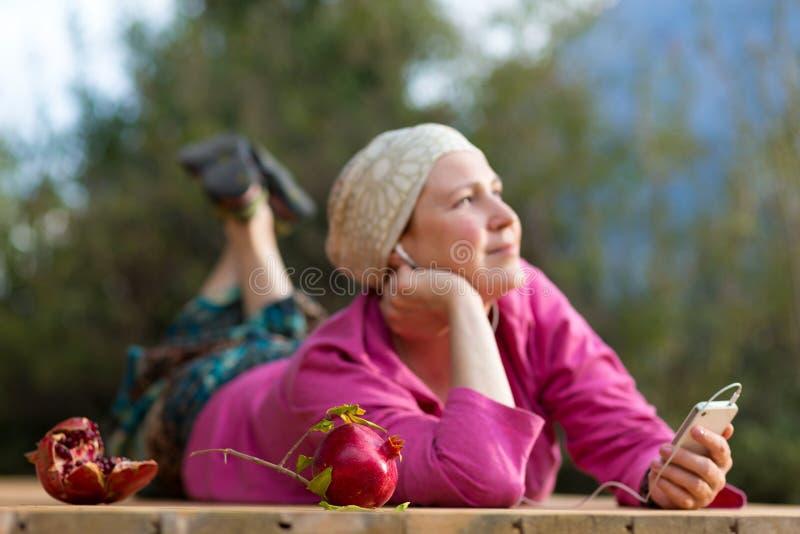 Uśmiechniętej kobiety słuchająca muzyka w słuchawkach na telefonie zdjęcia royalty free