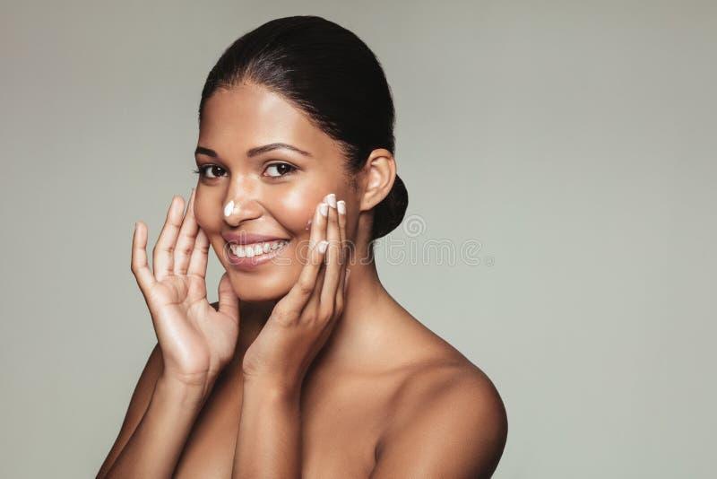 Uśmiechniętej kobiety wzorcowy stosuje moisturizer fotografia stock