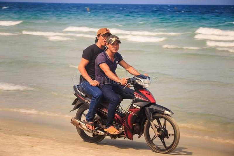 Uśmiechniętej mężczyzna turystów przejażdżki Chłodno motocykl na ocean plaży zdjęcie stock