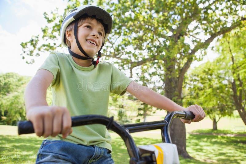Uśmiechniętej młodej chłopiec jeździecki bicykl przy parkiem zdjęcia stock
