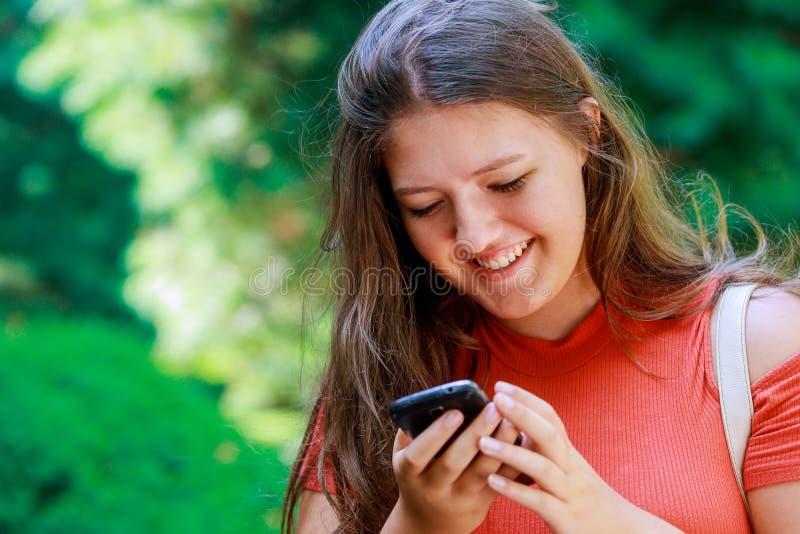 Uśmiechniętej młodej dobrej nastoletniej dziewczyny czytelnicze wiadomości w ogólnospołecznych sieciach telefon komórkowy fotografia stock