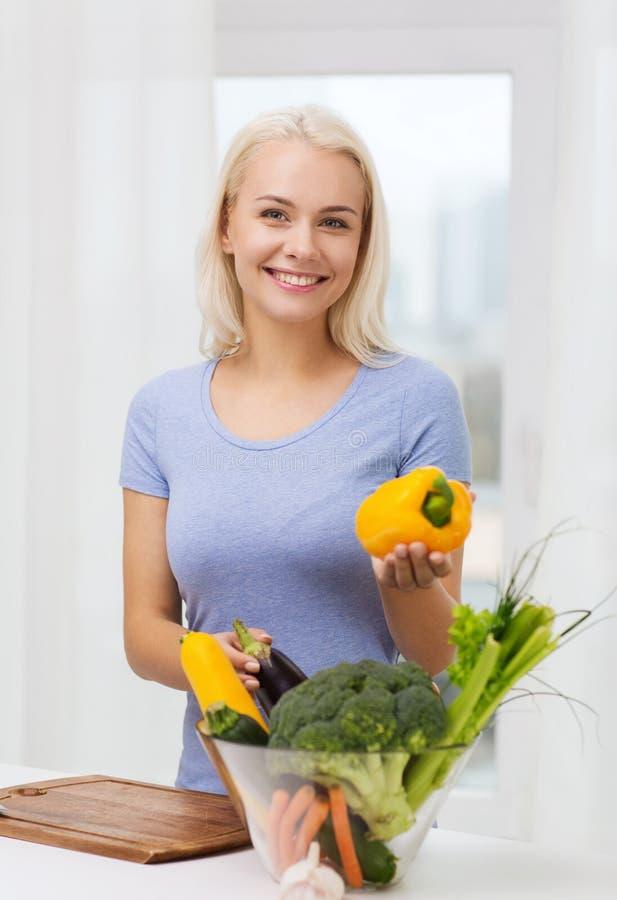 Uśmiechniętej młodej kobiety kulinarni warzywa w domu zdjęcia stock