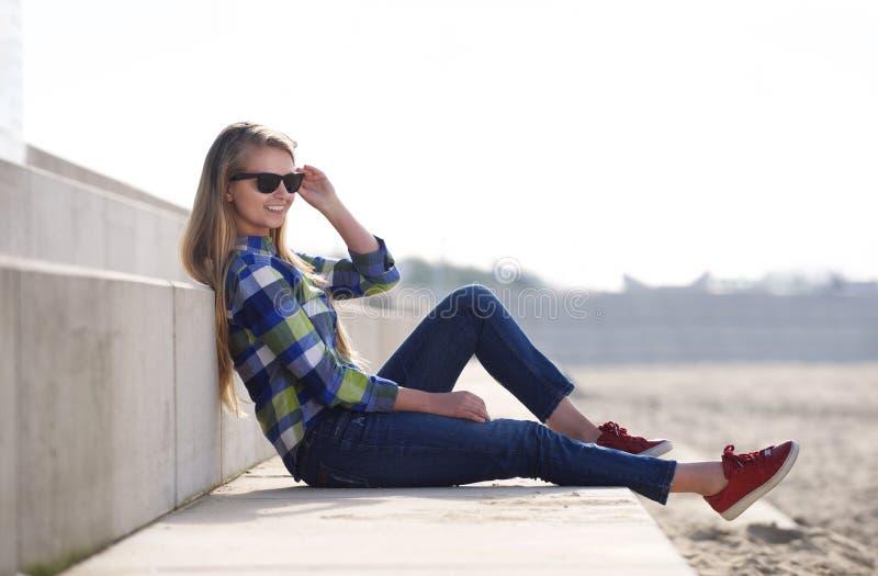 Uśmiechniętej młodej kobiety siedzący outside z okularami przeciwsłonecznymi zdjęcie royalty free