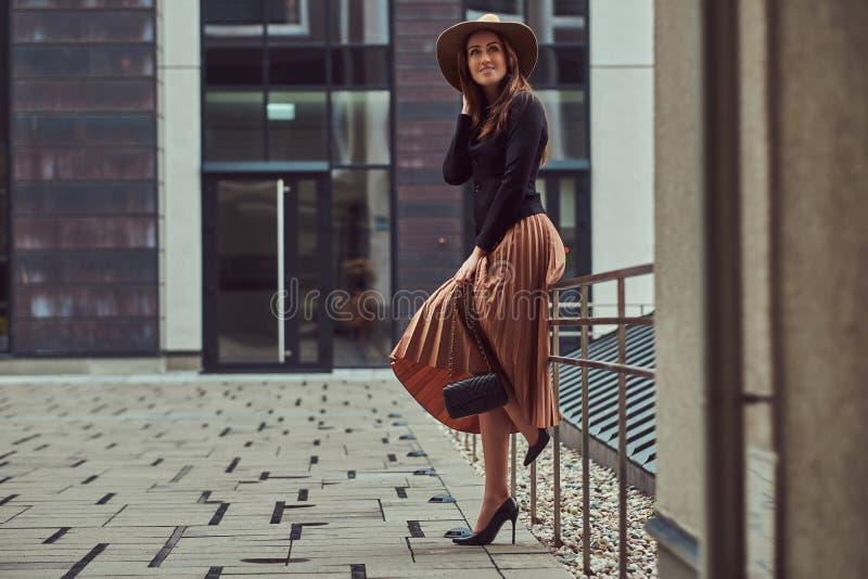 Uśmiechniętej mody elegancka kobieta jest ubranym czarną kurtkę, brown kapelusz i spódnicę z torebki sprzęgłowy pozować, podczas  obrazy stock