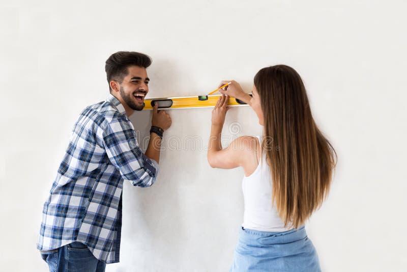 Uśmiechniętej potomstwo pary pomiarowa ściana z pozioma narzędziem, odświeżanie zdjęcia royalty free