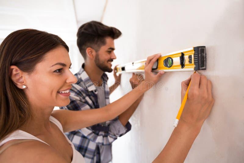 Uśmiechniętej potomstwo pary pomiarowa ściana z pozioma narzędziem, odświeżanie obraz stock