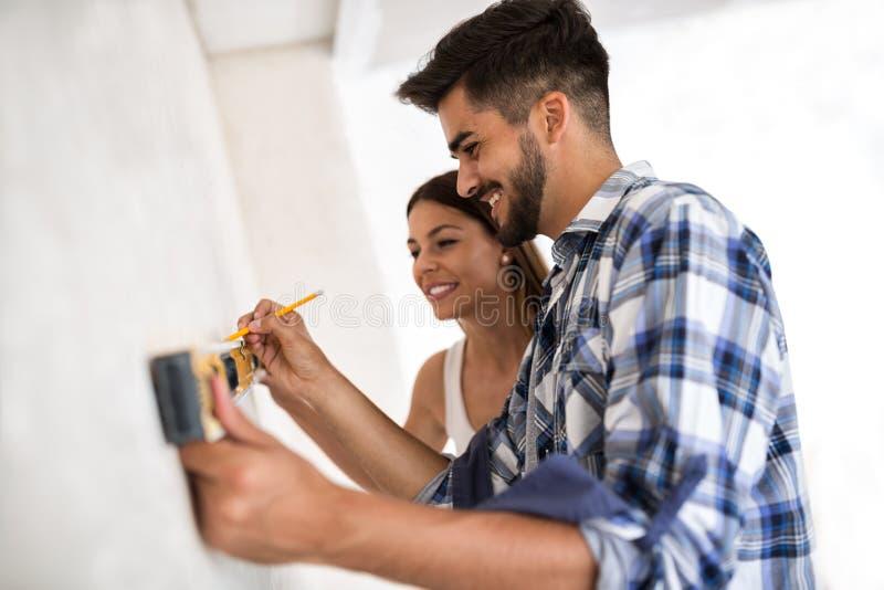 Uśmiechniętej potomstwo pary whit pozioma pomiarowy ścienny narzędzie, odświeżanie zdjęcia royalty free
