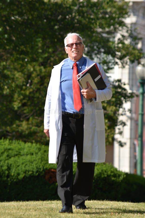 Uśmiechniętej Przystojnej Starszej samiec Lab żakieta Doktorski Jest ubranym odprowadzenie obrazy stock