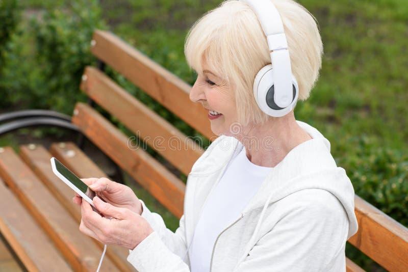 uśmiechniętej starszej kobiety słuchająca muzyka z hełmofonami zdjęcia stock