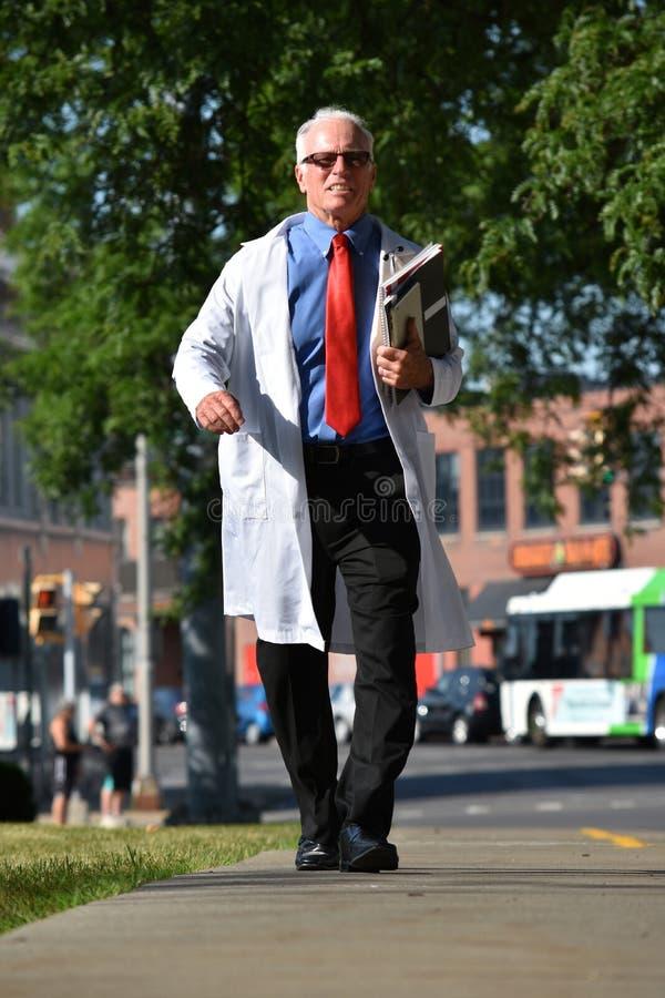 Uśmiechniętej Starszej samiec Lab Doktorski Jest ubranym żakiet Z notatników Chodzić zdjęcie stock