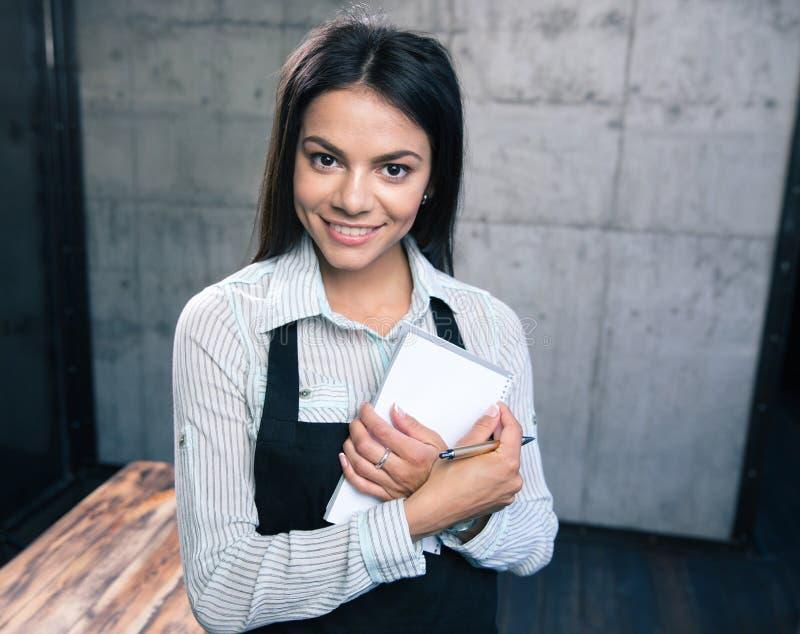 Uśmiechnięty ładny żeński kelner w fartuchu fotografia royalty free