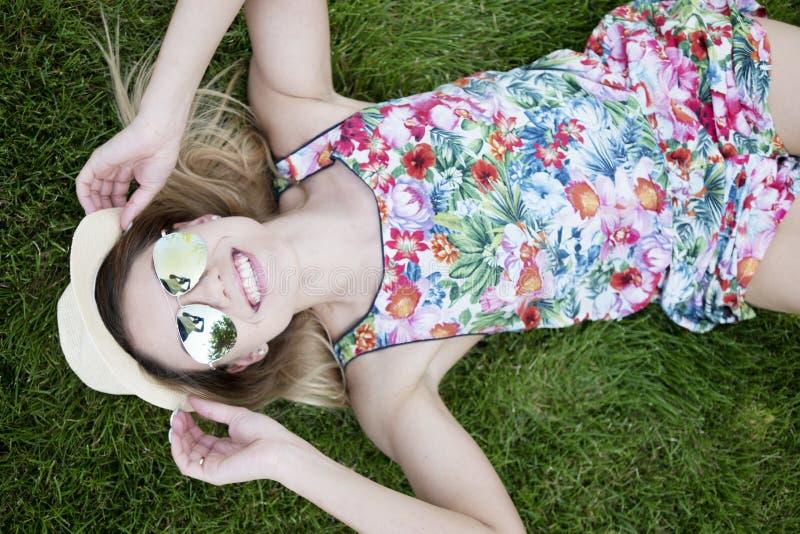 Uśmiechnięty Ładny młodej kobiety lying on the beach na trawach obraz stock