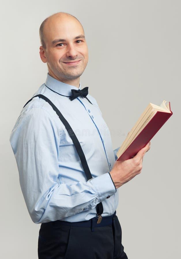 Uśmiechnięty łysy mężczyzna czyta książkę zdjęcie stock