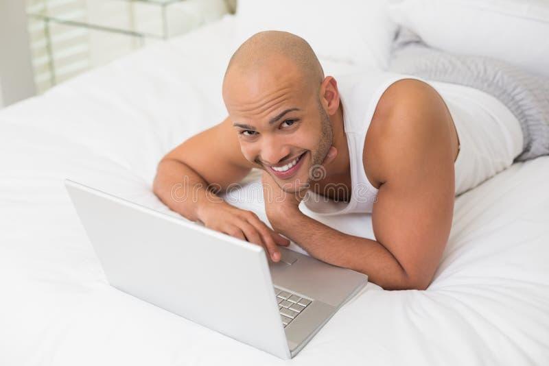 Uśmiechnięty łysy mężczyzna używa laptop w łóżku obrazy royalty free