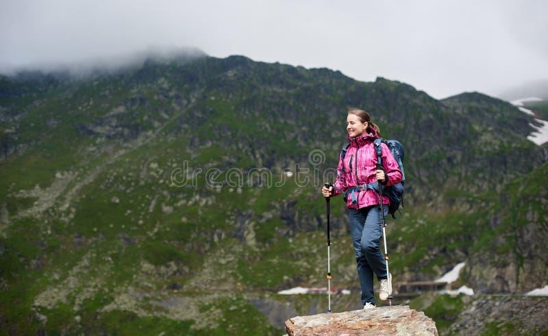 Uśmiechnięty żeński arywisty dojechania skały wierzchołek z pięknymi zielonymi górami w Rumunia zdjęcie stock