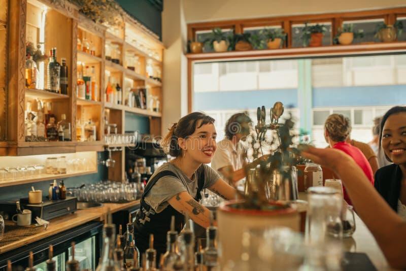 Uśmiechnięty żeński barman opowiada z klientami przy zakazuje kontuar zdjęcie royalty free