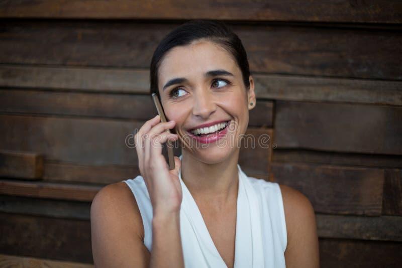 Uśmiechnięty żeński dyrektor wykonawczy opowiada na telefonie komórkowym obraz stock